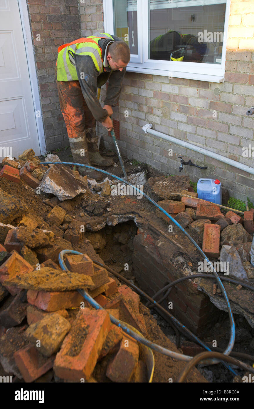 Workman digging to install water supply pipe - Stock Image