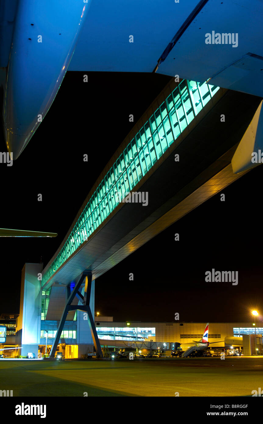 A nightime photograph of Gatwick Airports bridge over a taxiway - Stock Image