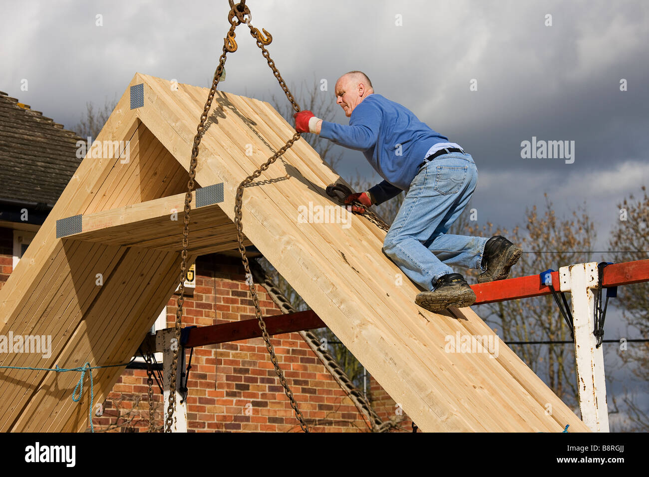 Attaching lifting chains from crane jib around timbers of the roof trusses, ready for them to be lifted from delivery - Stock Image