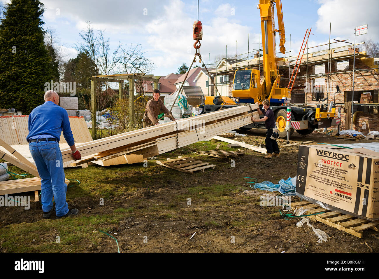 Workmen unloading delivery of roofing timbers from a consignment ready to build a roof - Stock Image