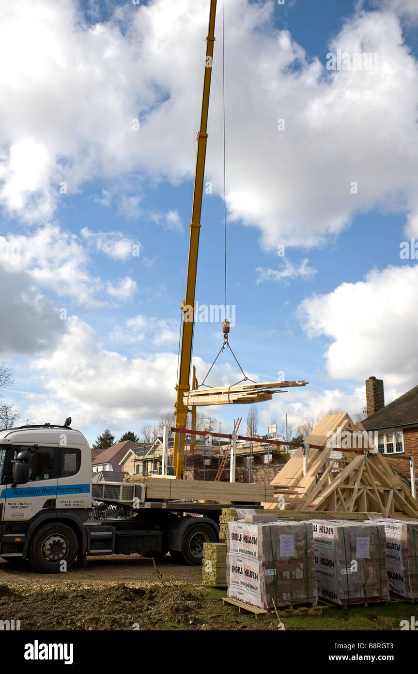 A crane being used to unload a delivery of roofing timbers made off site and delivered ready for use - Stock Image