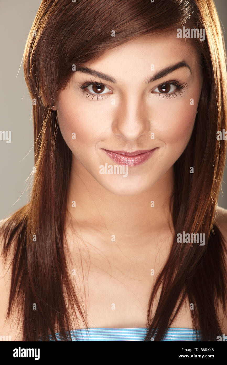 A happy young woman on gray background - Stock Image