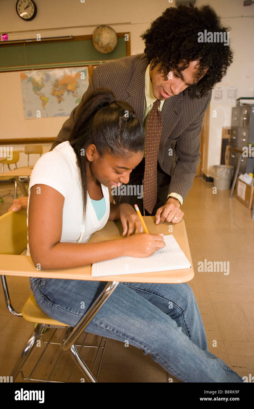 african american teacher in public american school helps teenage student solve a problem at her desk in classroom - Stock Image