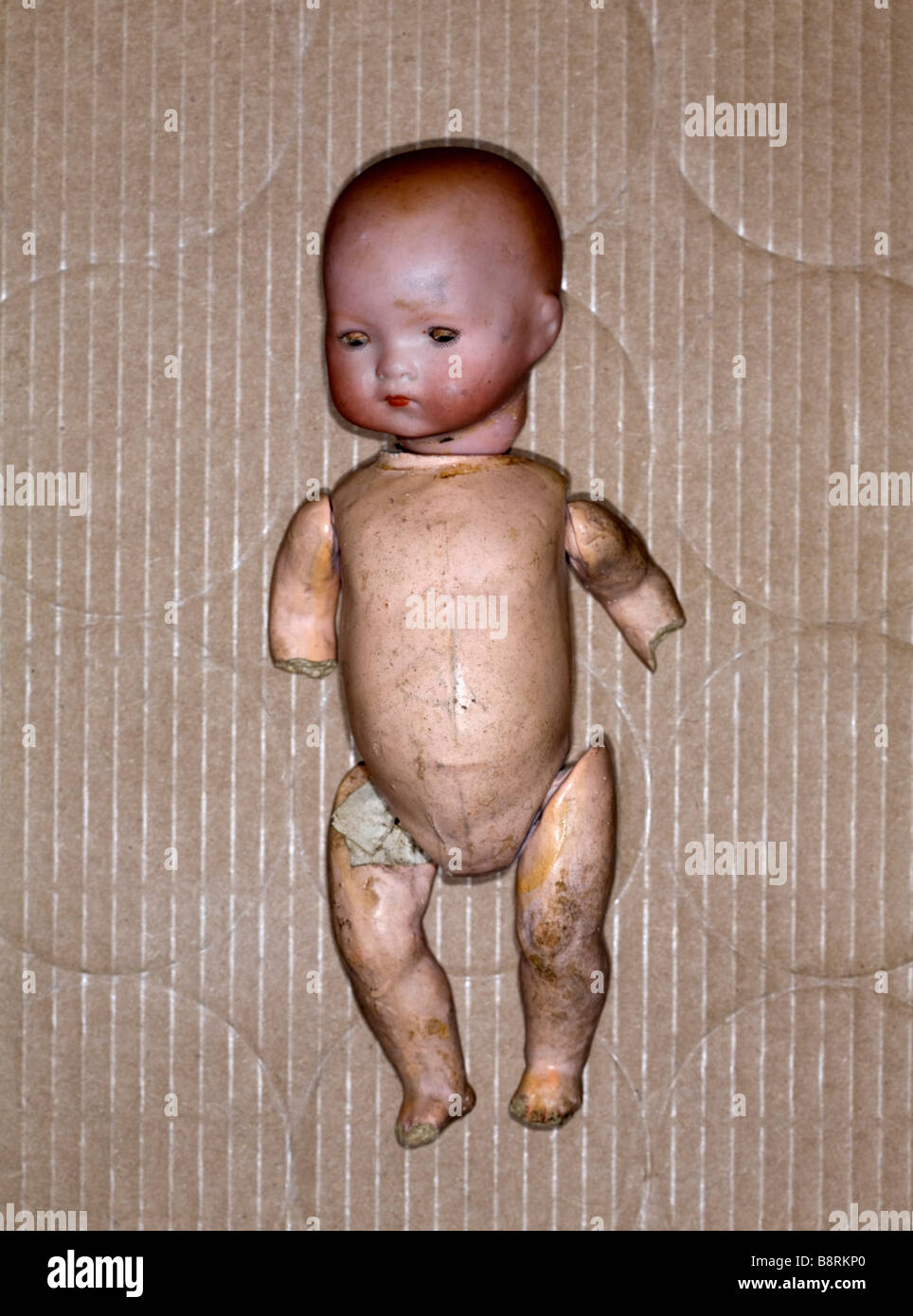 Studio shot of  damaged toy doll in a cardboard box. - Stock Image