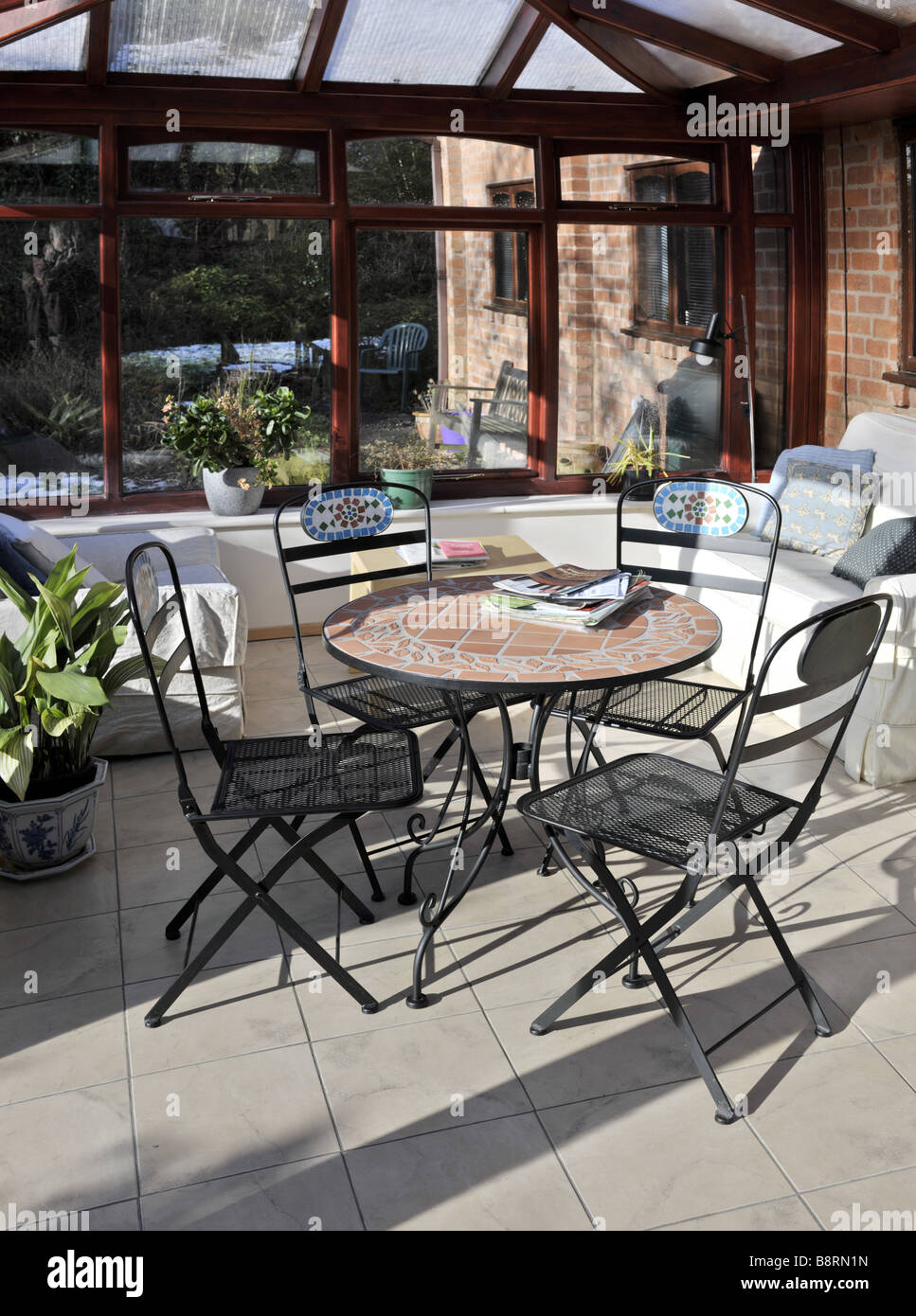 conservatory tables chairs plants room in house next to garden - Stock Image