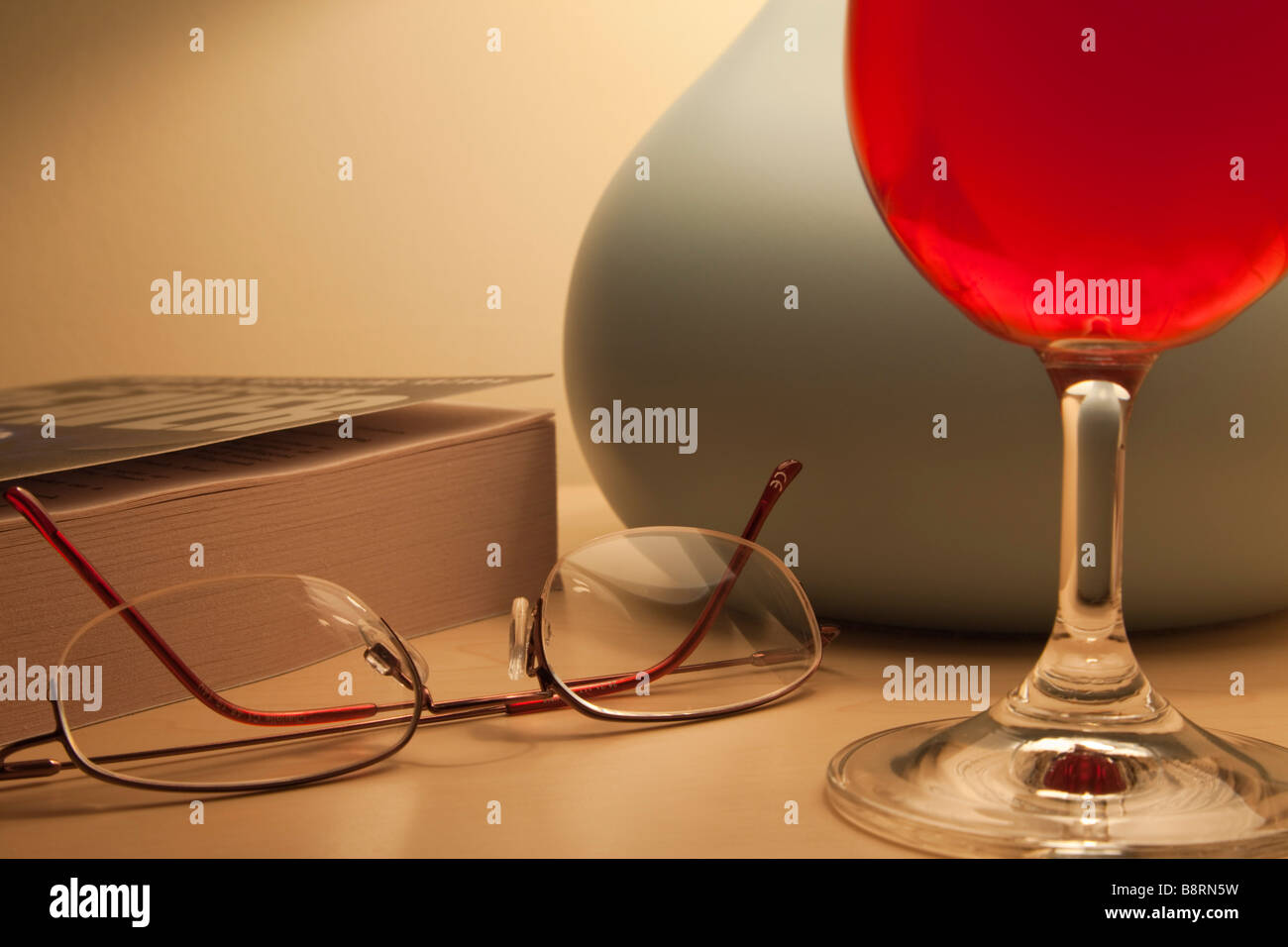 Everyday homely hygge scene with a glass of red wine by lit bedside table lamp paperback book and reading glasses - Stock Image