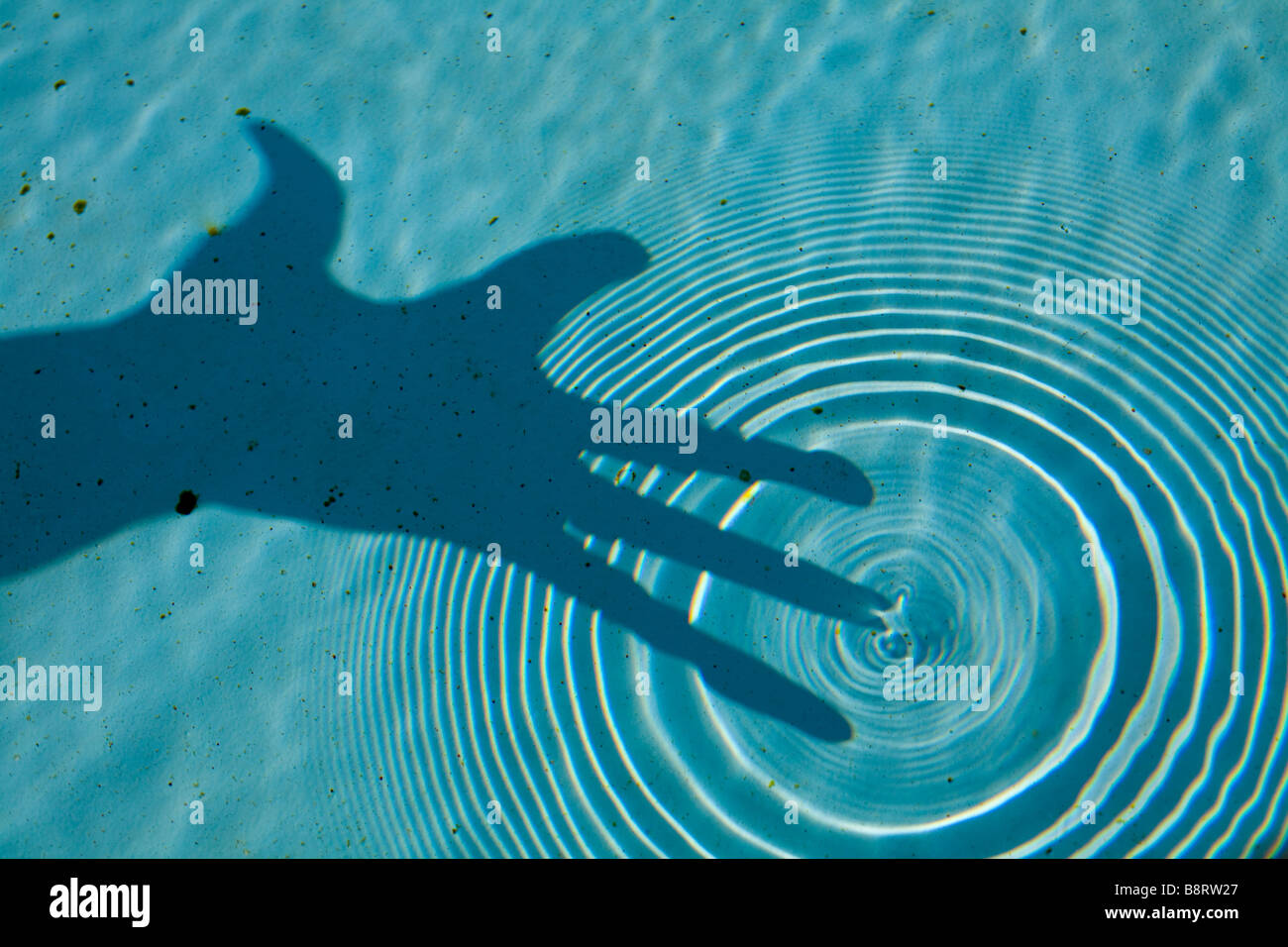 The effect of a finger touching the water in a pool. We can see the circular wade created and the shadow of the - Stock Image