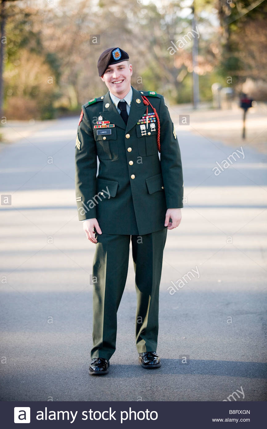 Full length of young army sergeant wearing his formal uniform standing in the middle of a quiet neighborhood street. - Stock Image
