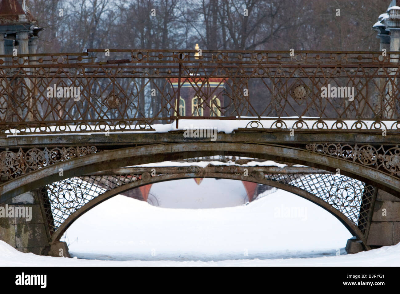Two weathered metal forged arch bridges covered with snow in winter park. Stock Photo