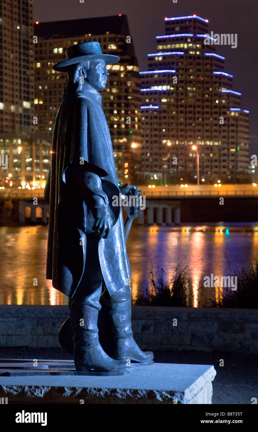 A bronze Stevie Ray Vaughn statue overlooks Downtown Austin at night - Stock Image