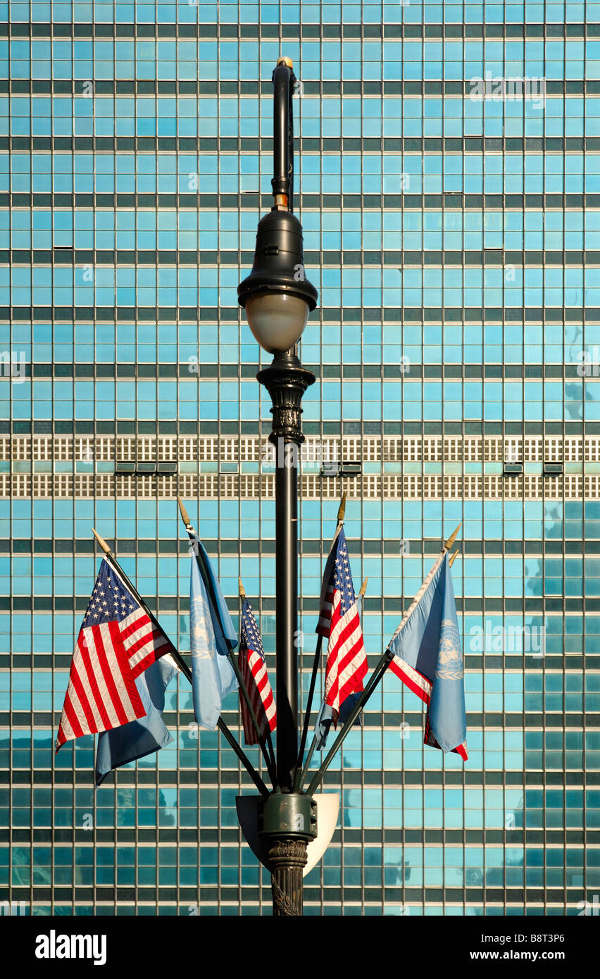 Lamp post with UN and US flags in front of the glass facade of the United Nations headquarters, UNO, New York, USA Stock Photo