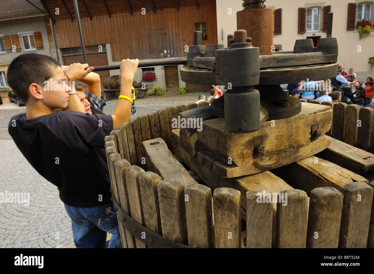 Two Swiss boys operate an old wine press at a wine festival - Stock Image