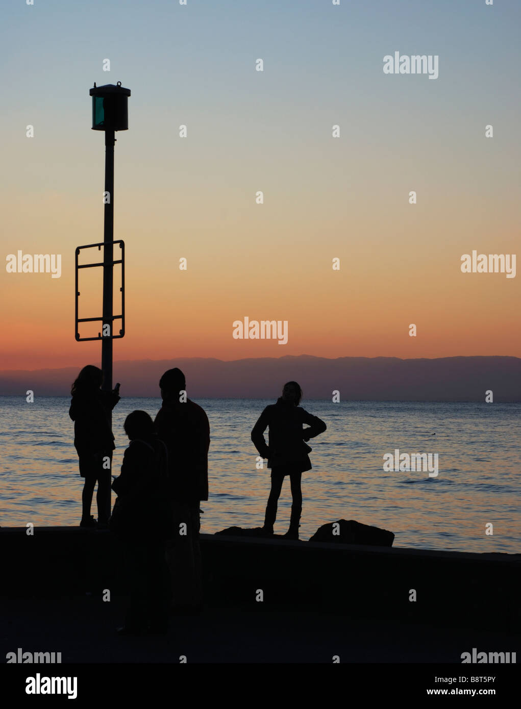 View of the sunset over Lac Leman as viewed from Lausanne, Switzerland. Unrecognisable family in the foreground - Stock Image