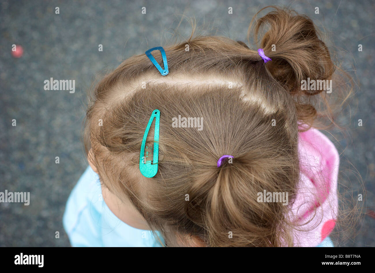 High Angle Close up View of Little Girls Head with Barettes and Pigtails - Stock Image