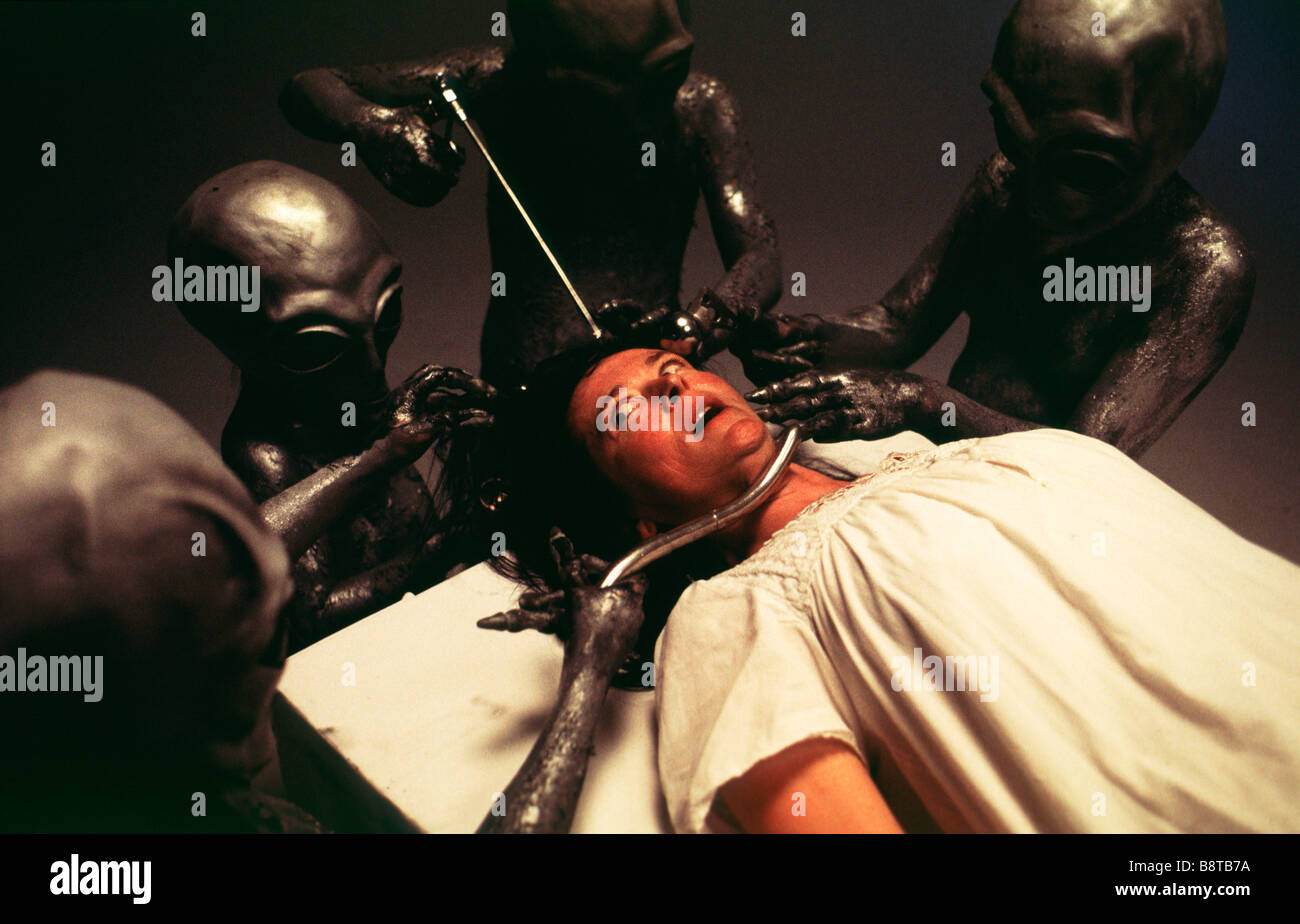 Alien abduction. Alien beings examine a human woman on their spaceship - Stock Image