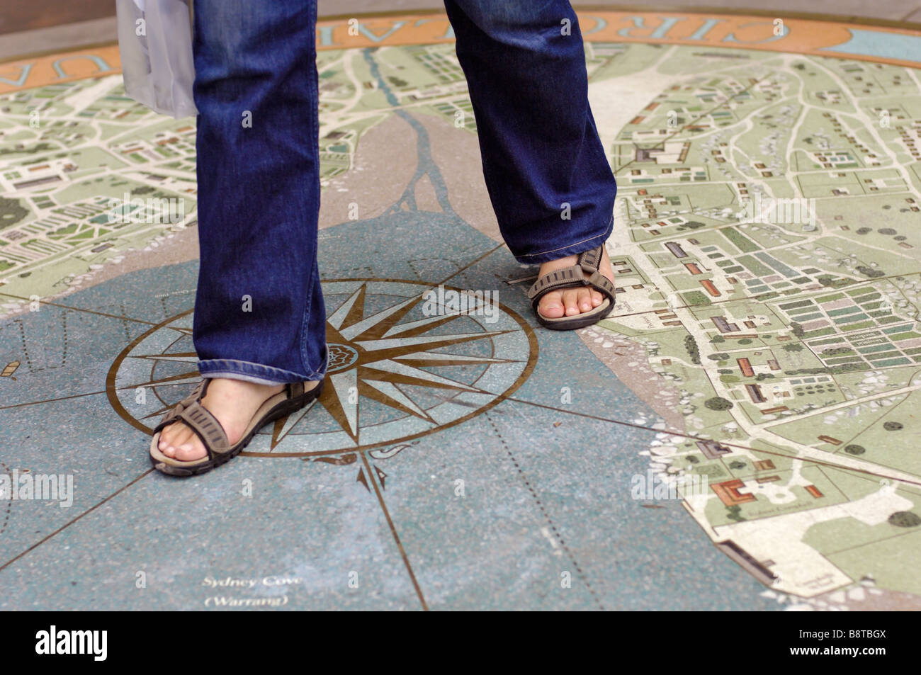 A young woman steps over a mosaic representing Sydney Cove, Sydney, New South Wales, Australia - Stock Image