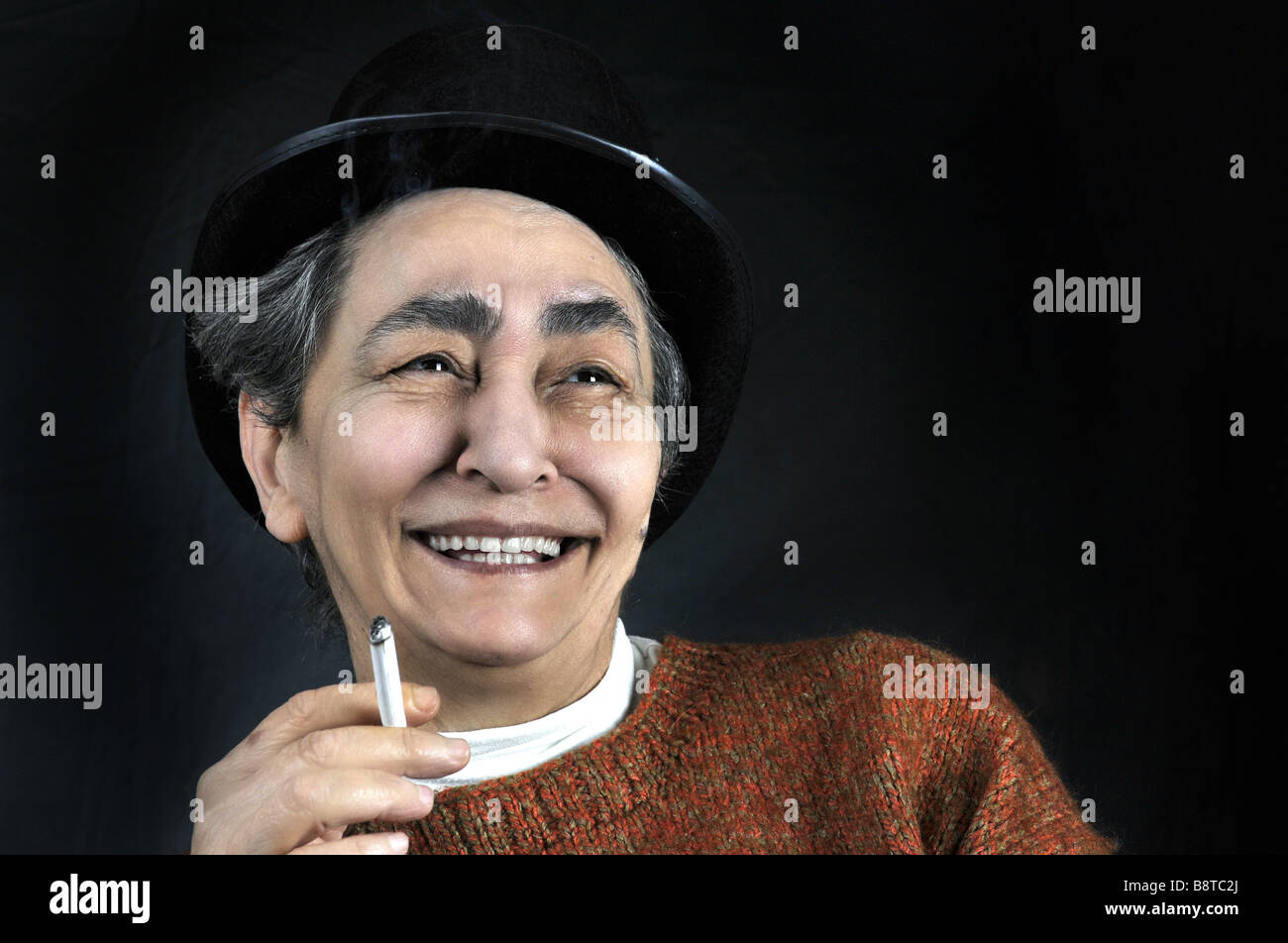 Portrait on black backround of artistic mature smiling woman with hat and cigarette in her hand Stock Photo
