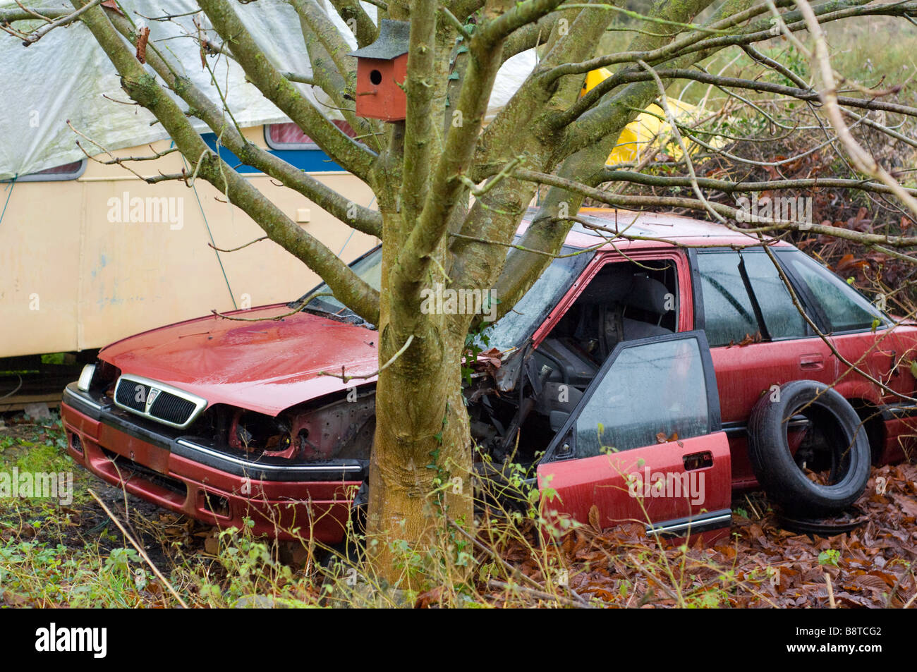 An abandoned car and caravan, and a bird nesting box, on waste ground in Somerset, England. - Stock Image