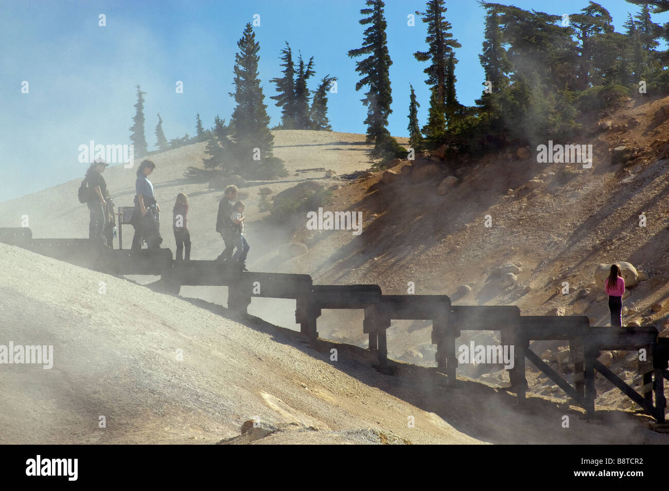 Tourists on boardwalk over fumaroles in Bumpass Hell area at Lassen Volcanic National Park California USA - Stock Image
