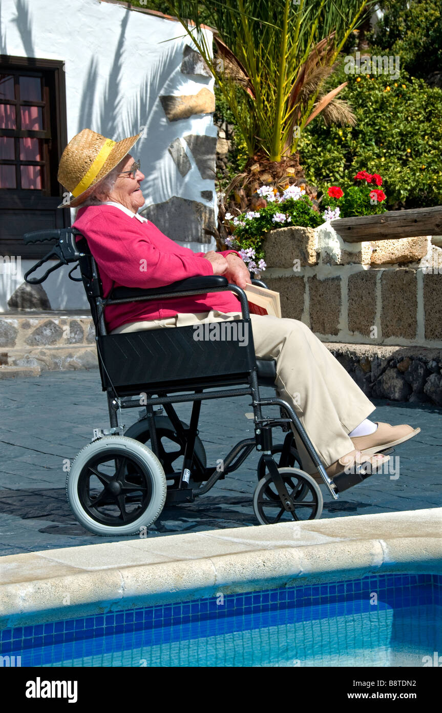 Contented elderly disabled lady sitting in her wheelchair reading a book in a sunny holiday vacation poolside setting - Stock Image