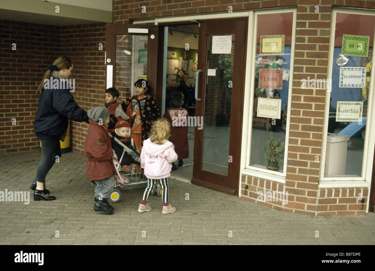 Mother entering school with her three children - Stock Image