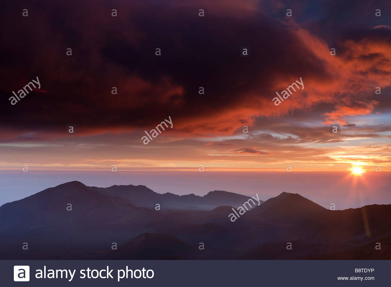 The sun rises over the Pacific Ocean, lighting up the sky above the crater in Haleakala National Park, Maui, Hawaii. - Stock Image