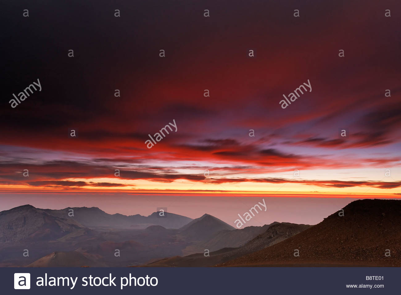 An approaching storm results in a fiery sunrise over the Haleakala crater in Haleakala National Park, Maui, Hawaii. - Stock Image