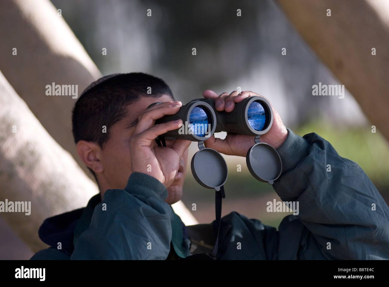 An Israeli soldier using his binoculars near Gaza border southern Israel - Stock Image