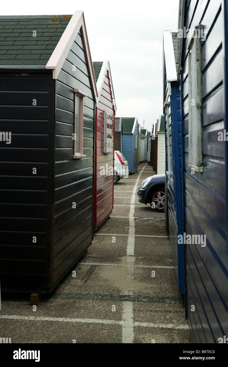 beach huts stored around parked cars illustrating a competition for space between cars and housing - Stock Image