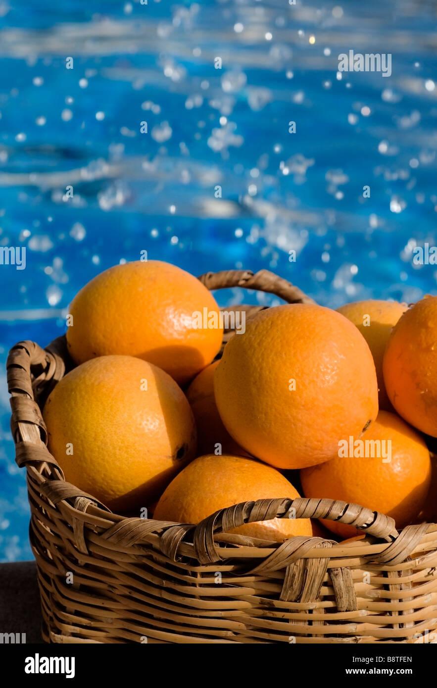 Basket of sunny Spanish oranges with swimming pool and splashing water behind - Stock Image