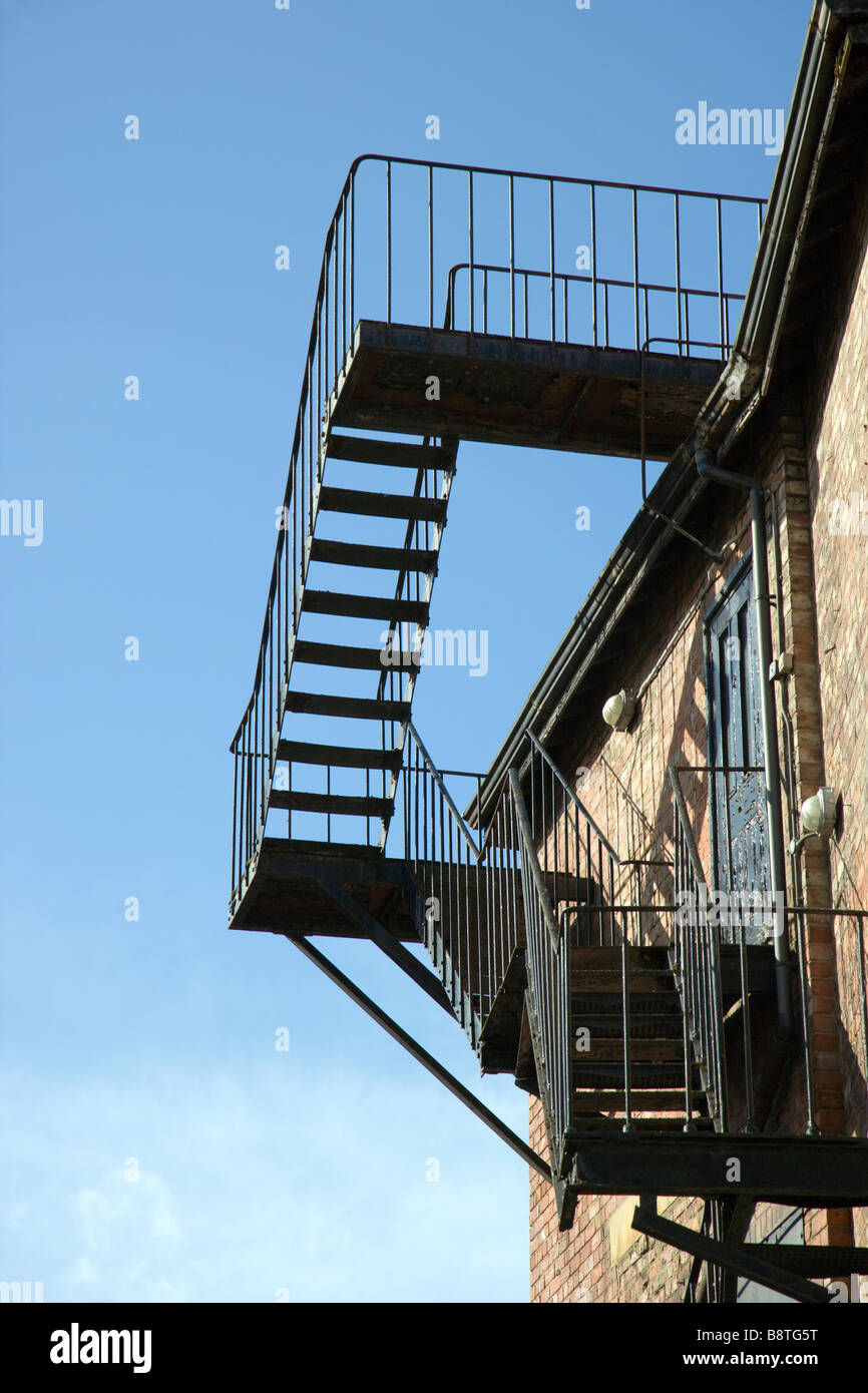 External fire escape, metal steps to roof safety against a blue sky Stock Photo