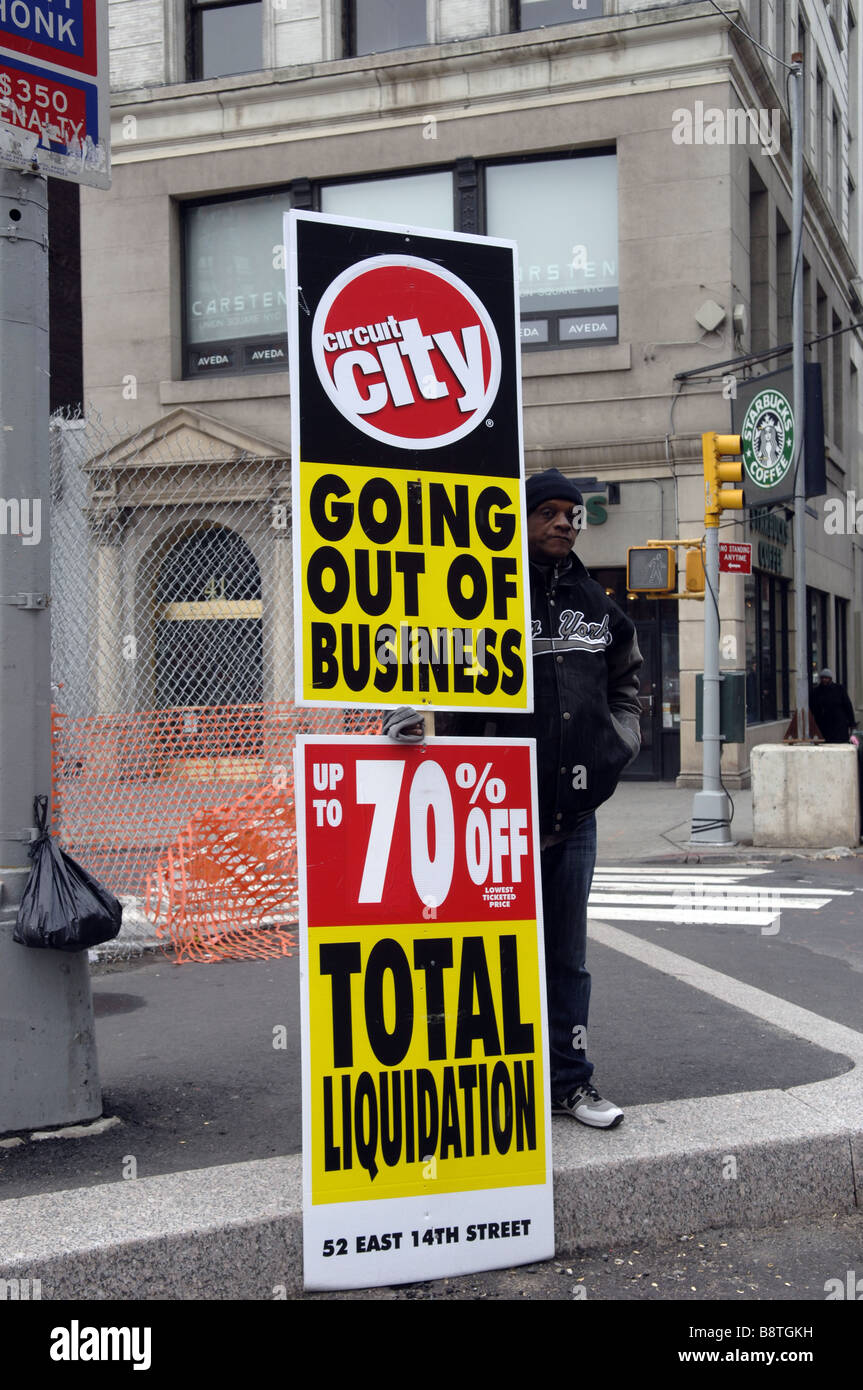 A Worker Holds Up Sign Advertising That The Circuit City Electronics Store Is Liquidating In