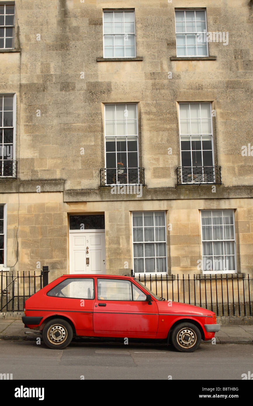 An old red tatty cheap car parked outside an expensive luxury Stock ...