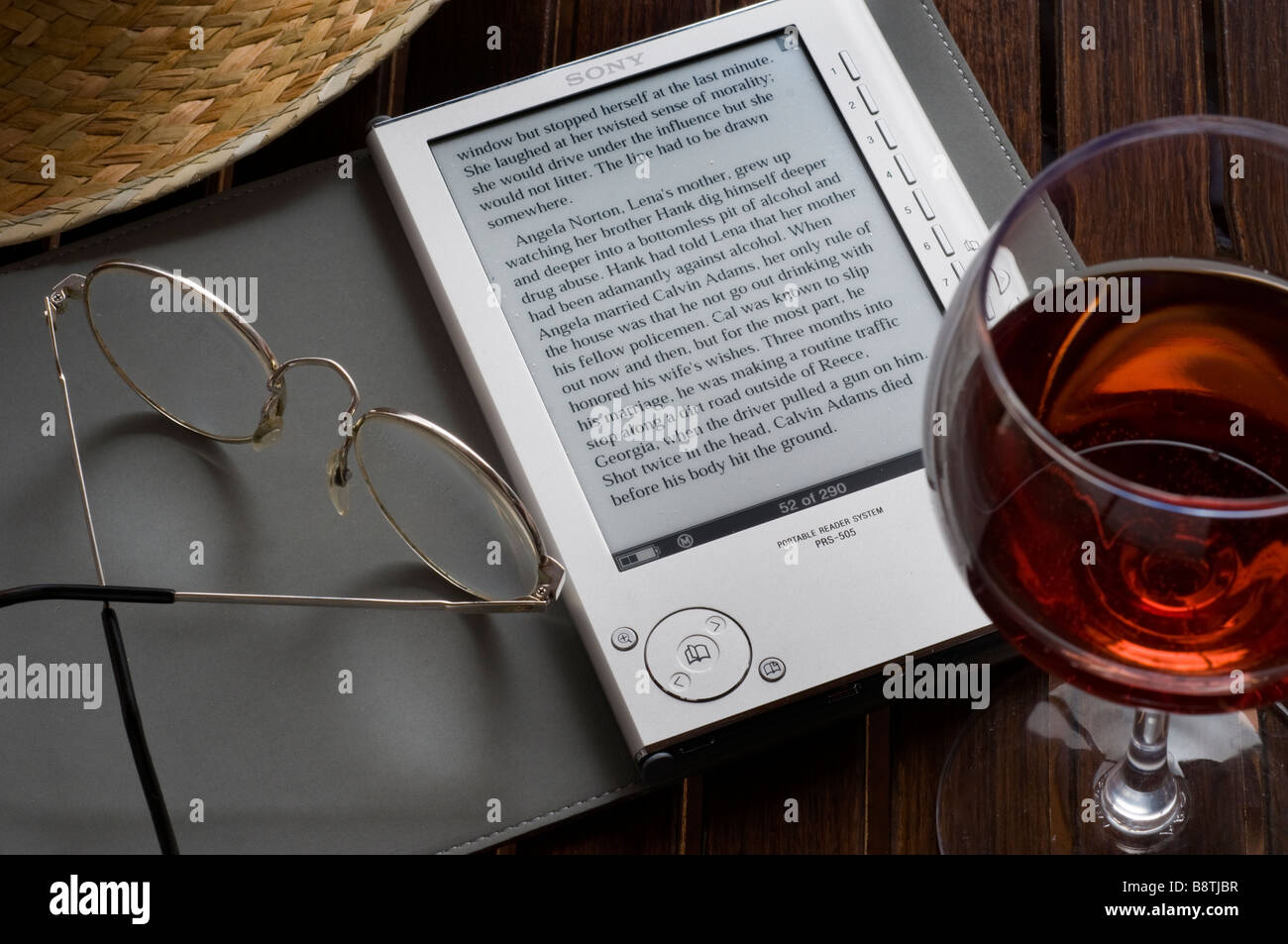 Sony eReader, an electronic portable book reading device on terrace table, with glass of wine straw hat and reading - Stock Image