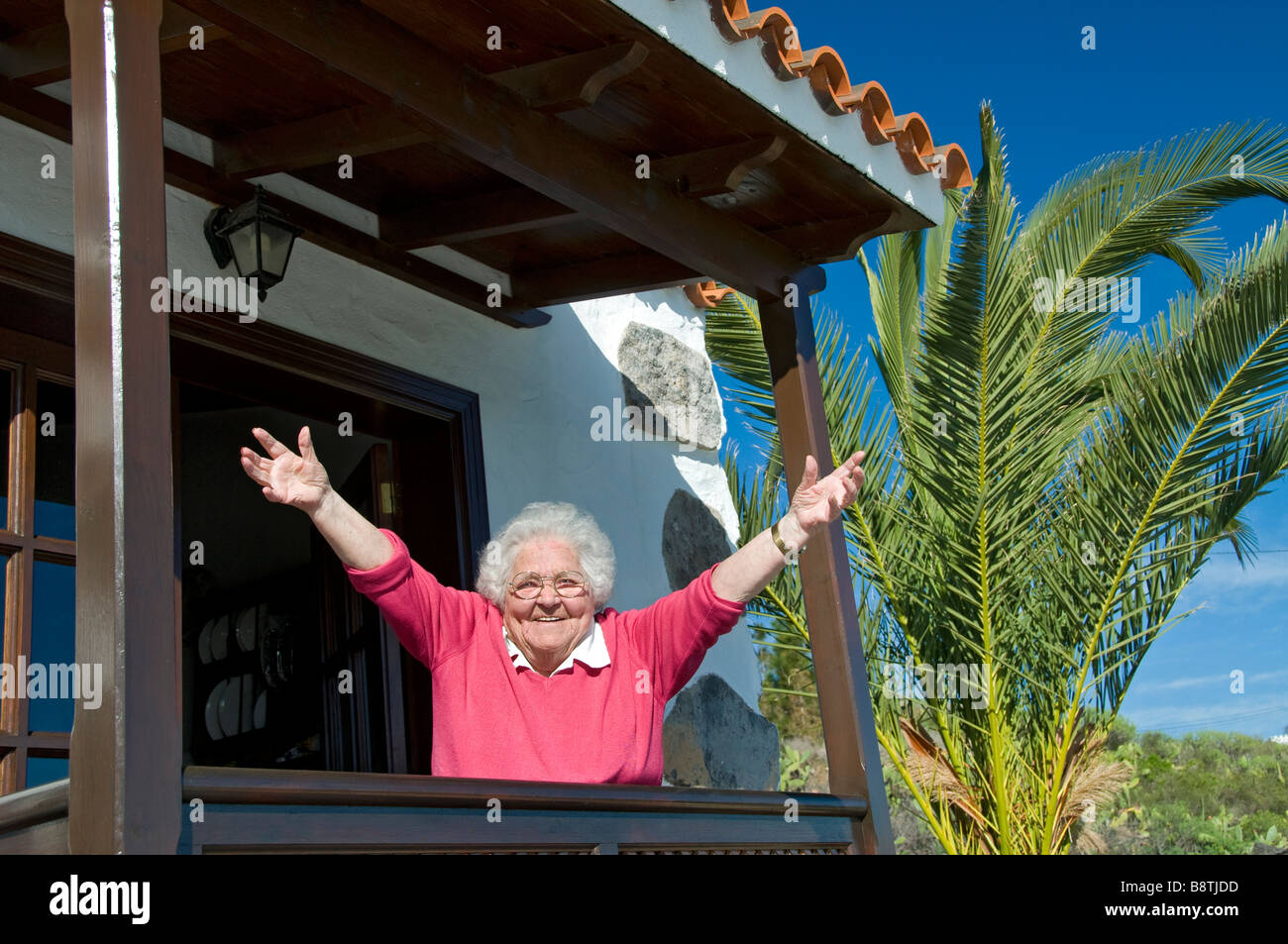 Happy elderly lady with vitality stretches out her arms enjoying a holiday visit to her sunny vacation holiday villa - Stock Image