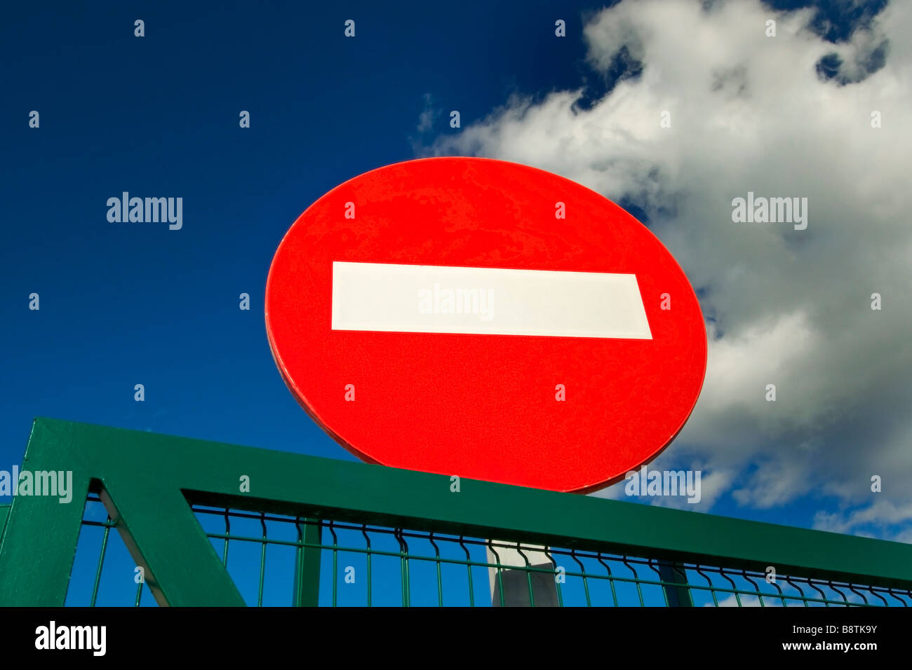 Concept  Red No Entry sign and blue sky at entrance to secure metal fenced facility - Stock Image