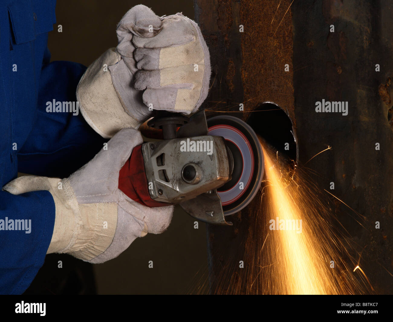 Hands with protective gloves using angle grinder on iron sparks heat friction - Stock Image
