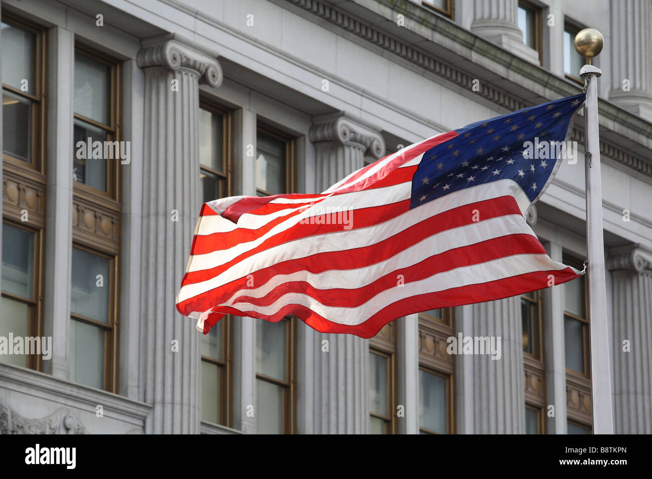 American flag flying in front of federal style architecture - Stock Image