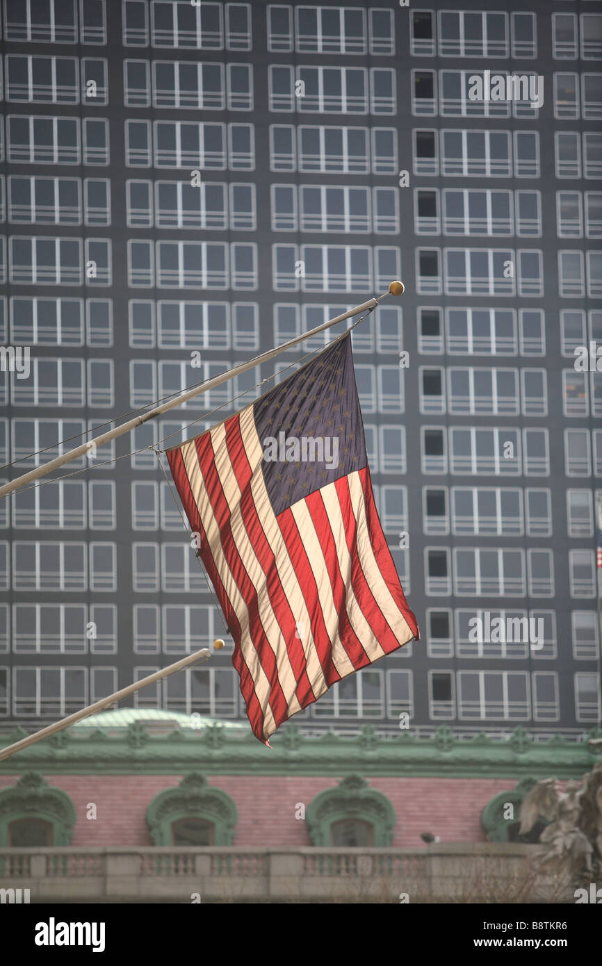 American flag flying in front of two contrasting buildings - Stock Image