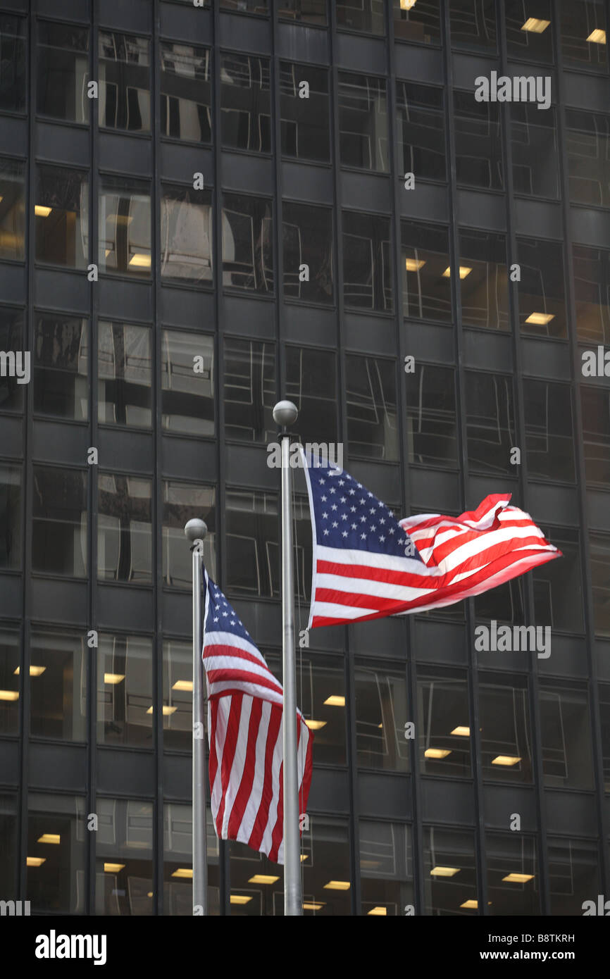 Two American Flags in front of a black glass building - Stock Image