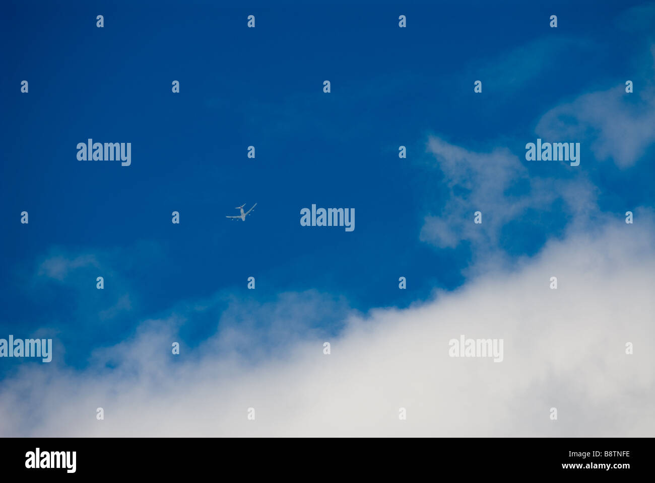 photograph of passenger jet aircraft against blue sky - Stock Image