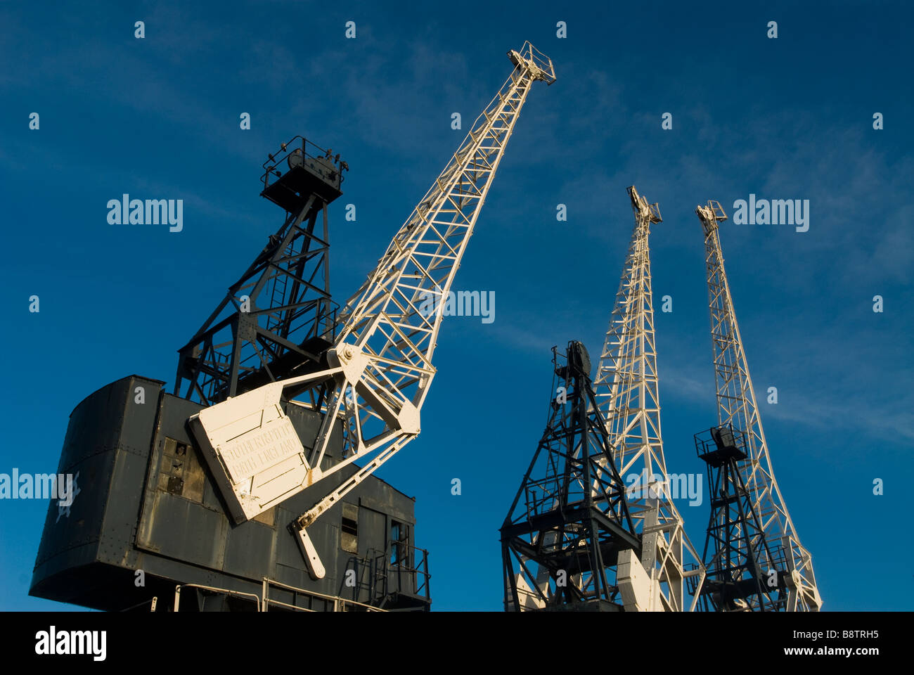 photograph of three cranes against blue sky - Stock Image