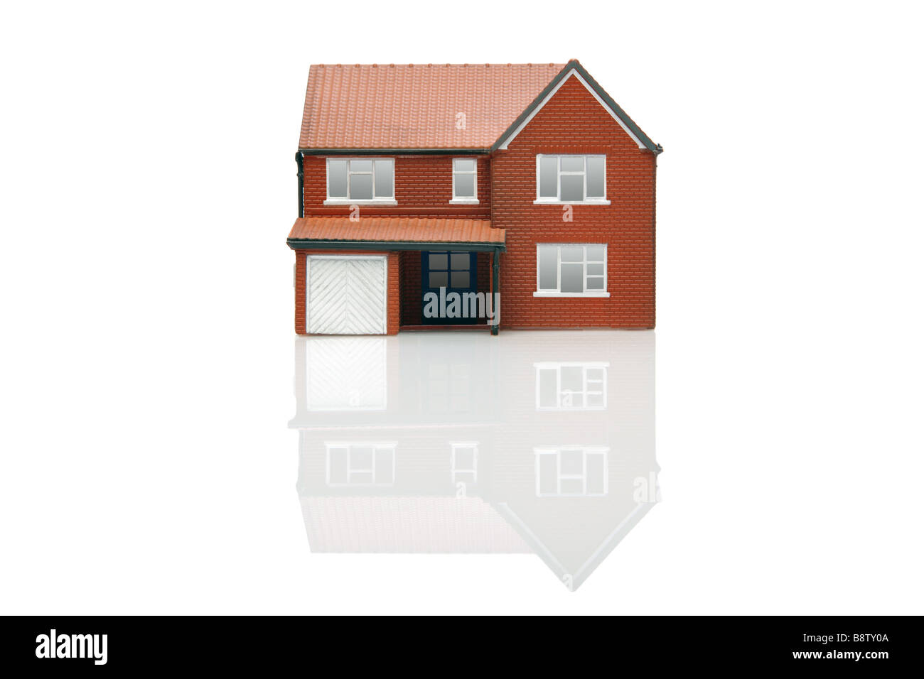 A model house isolated on a white background with reflection - Stock Image