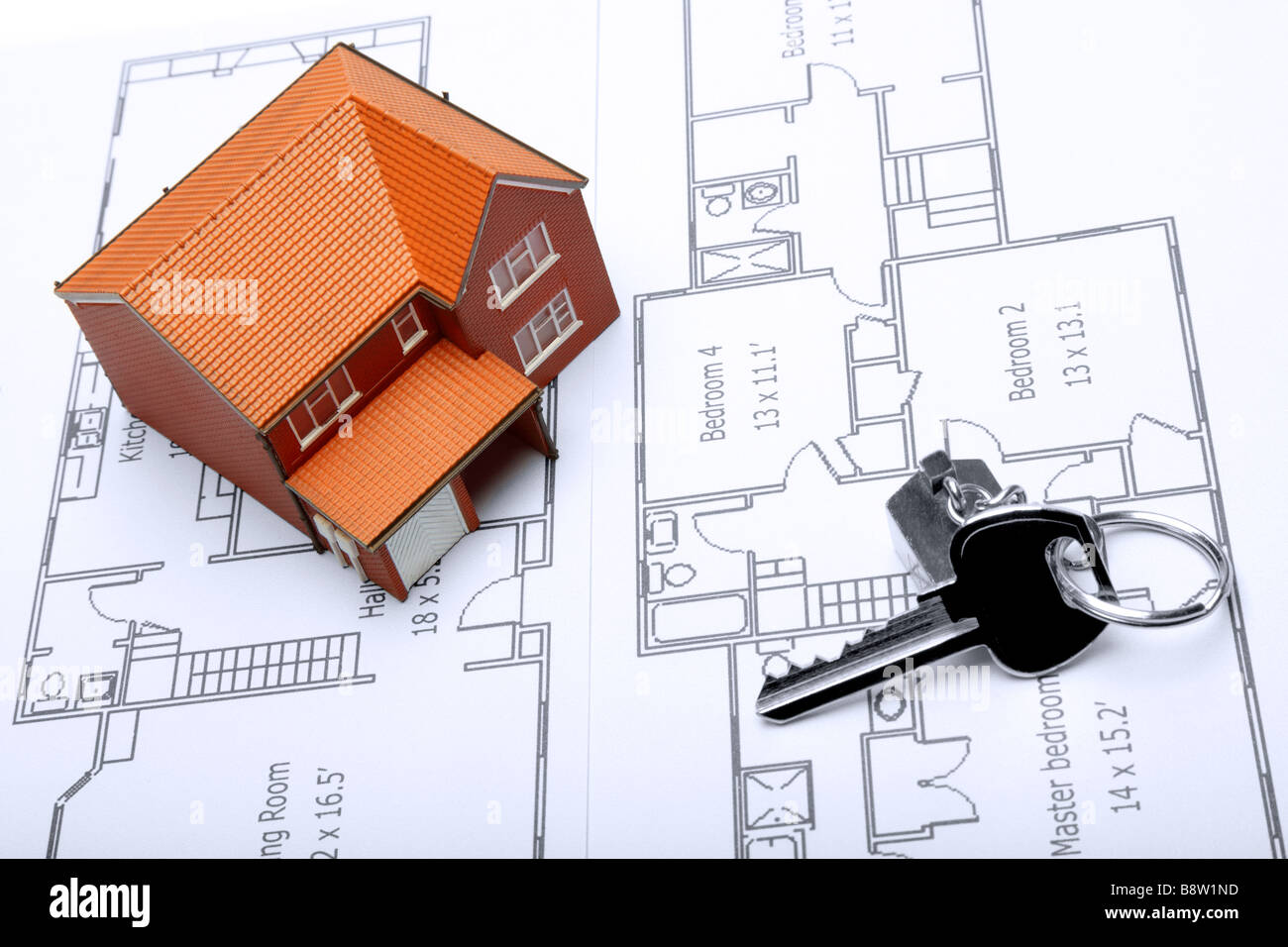 A model home and house key on architectural floor plans for an extension Stock Photo