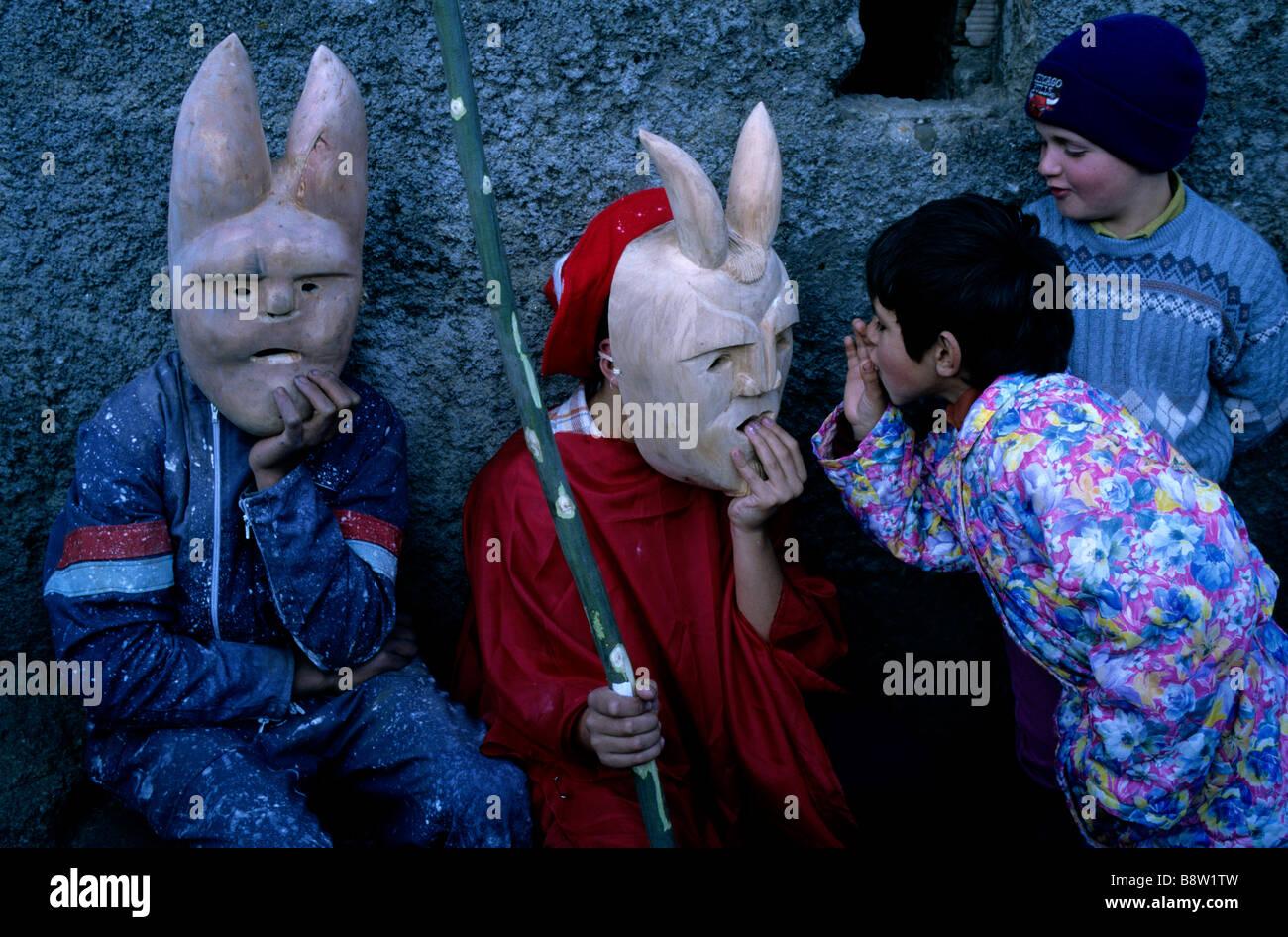 "Children tease two masked ""devils"" during the Caretos de Lazarim Carnaval festival in central Portugal's Douro region Stock Photo"
