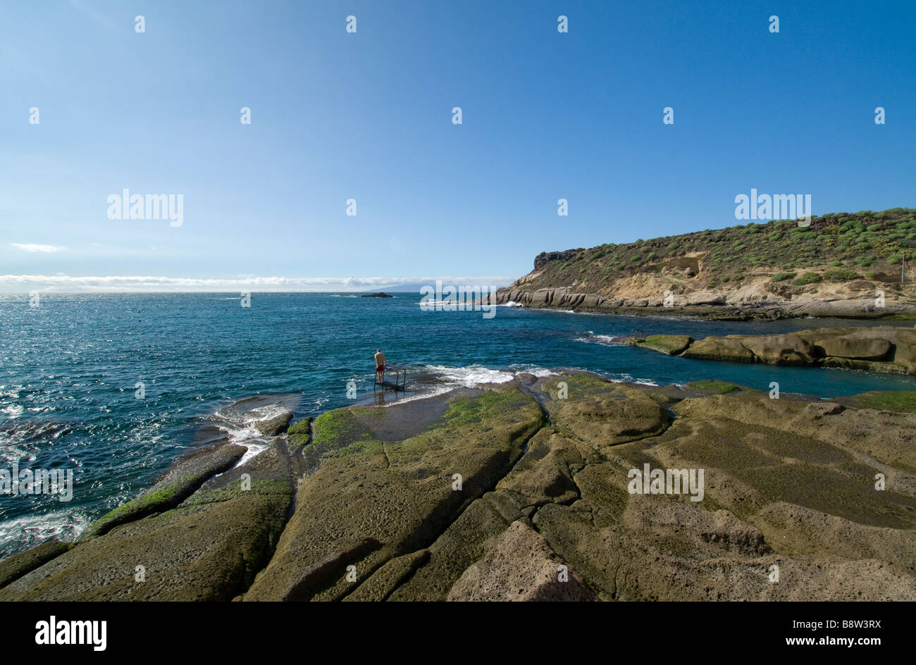 Lone bather standing on diving board looking out to sea at La Caleta Tenerife Canary Islands Spain - Stock Image