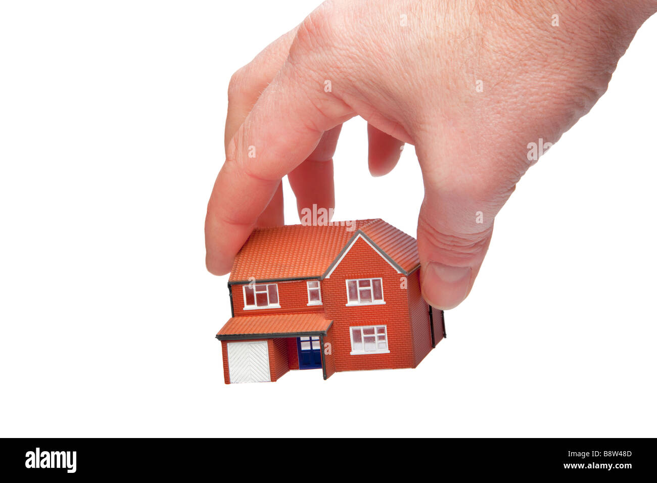 Hand picking up a small house isolated on a white background - Stock Image