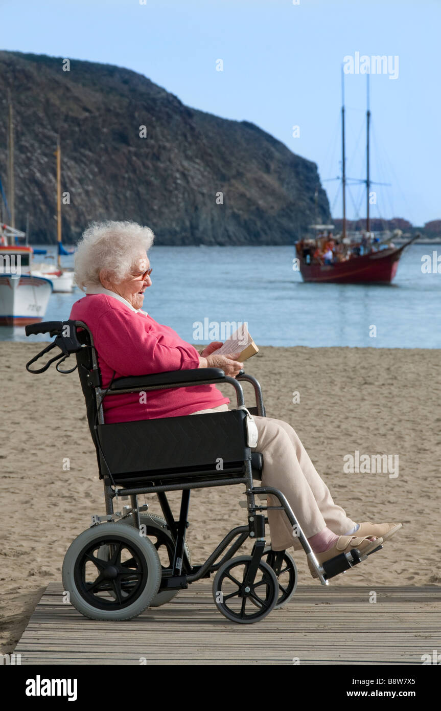 Contented elderly disabled lady sitting in her wheelchair reading a book in a sunny holiday vacation beach seaside - Stock Image