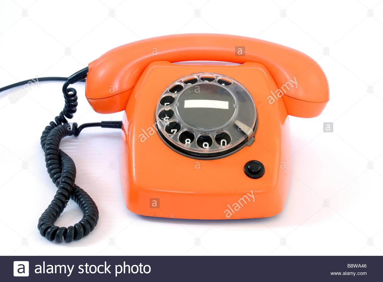 Orange 1970's style telephone on a white background. - Stock Image