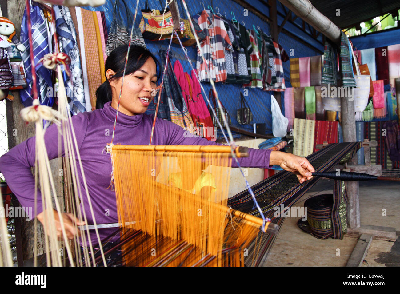 Asian People. Vietnamese woman weaving colourful scarf, carpet and other handicrafts in Dalat. Vietnam - Stock Image